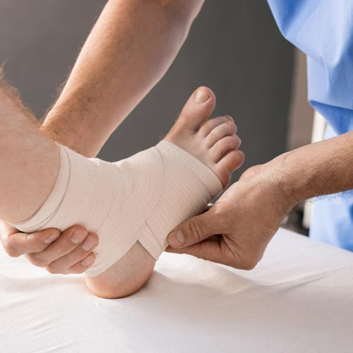 Doctor wrapping a patients foot and ankle